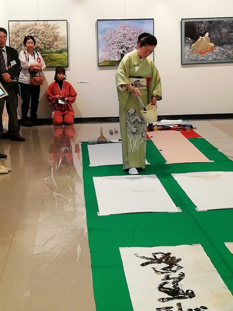 Kimonoon pukeutunut nainen maalaa suurella siveltimellä japanilaista kanjimerkkiä.