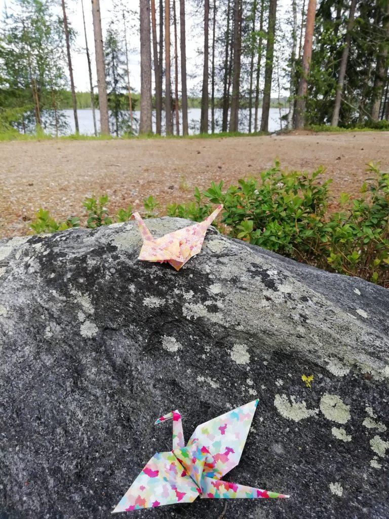 Kaksi origamilintua kivellä. Taustalla näkyy järvi.