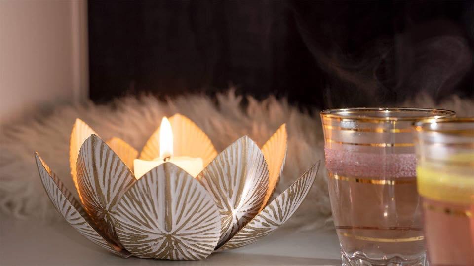 Lotuskukka, jonka sisällä palava kynttilä.