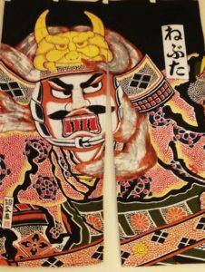 Hiukan pelottavan näköinen Neputa-festivaalin hahmo kuvattuna noren-oviverhoon