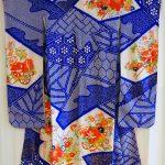 Silkkinen kimono sinisellä pohjalla oransseja kukkakuvioita.